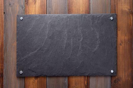 black slate stone at wooden background texture surface Banco de Imagens