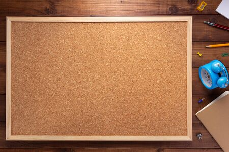 cork board and stationery supplies on wooden table background texture