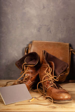 travel vintage old boots shoes at wooden desk table near concrete wall background texture surface Stock Photo