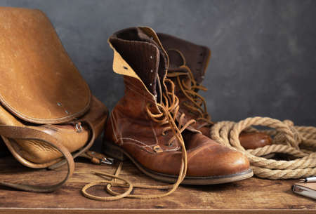 old leather travel vintage boots shoes and bag at wooden table, with wall background texture