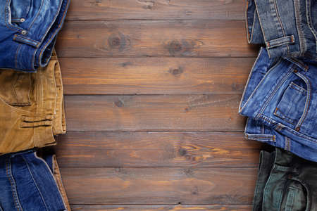 Denim jeans on old wooden background texture table surface. Top view