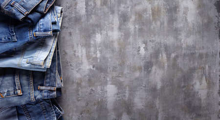 Denim jeans on old abstract background texture of table surface