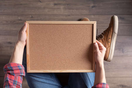 Men's hand holding corkboard frame. Male hand and cork board, top view