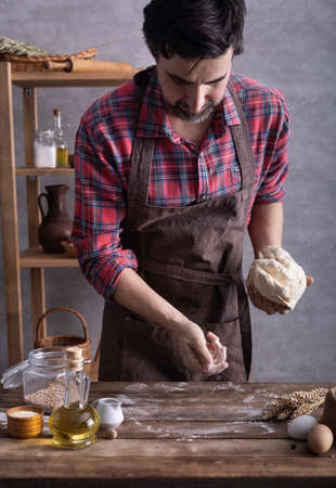 Baker man kneading or making dough and bakery ingredients for homemade bread cooking at table. Bakery concept and wooden table background texture