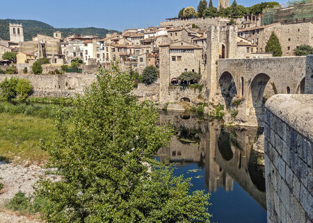 spanned: Medieval fortress town Besalu protected by powerful high stone walls , river, chkrez to the fortress gate which spanned stone arch bridge .