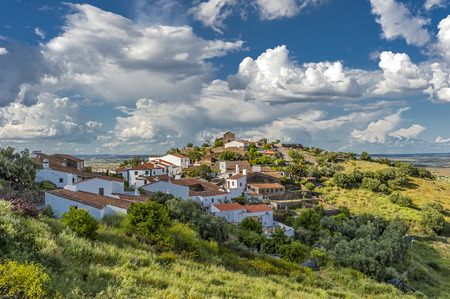 Portugal , the District of Evora . Immersed in the green village of Monsaraz outside walls. Bright , sunny spring day , beautiful clouds . Stock Photo