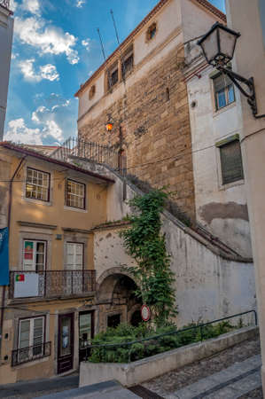 sawn: Portugal, Coimbra. Courtyards and streets of the old city in the evening. Stone sidewalks and streets. The walls are made of sawn limestone blocks, partially plastered. Editorial