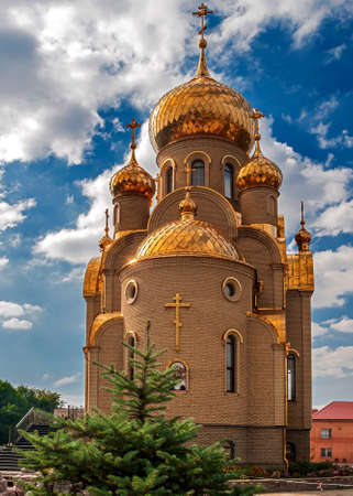 gilt: Ukraine, Khartsizk . Orthodox Church of the Iberian Icon of the Mother of God . Holy spring . The gilt domes and roof . Bright sunny day , blue sky with small clouds.