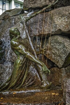 scald: Norway , Bergen . The foot of the monument - fountain to famous Norwegian composer and violinist Ole Bull . Bronze sculpture Scald playing the mythical harp.