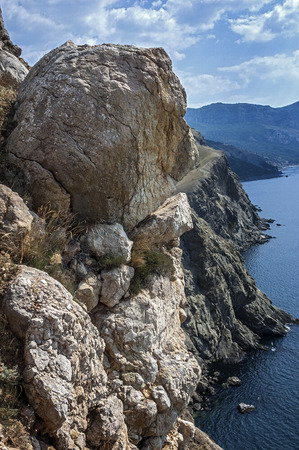rare rocks: Russia Crimea. Rocks which snap into the sea near Balaklava. Hot Crimean sunscorched grass rare green bushes mozhevelnik. Huge boulders miraculously hold on a slope.