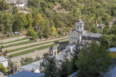 tier: Bakhchisaray , Crimea , Russia . Holy - Assumption Orthodox cave Monastery .The lower tier of the monastery. One of the new church , a small cemetery , outbuildings , land for vegetable gardens . Stock Photo