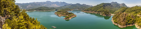 Turkey . Panorama . Huge deep lake in the mountains . Rocky coast with pine trees growing on them . Clean water, allowing breeding trout. Stock Photo