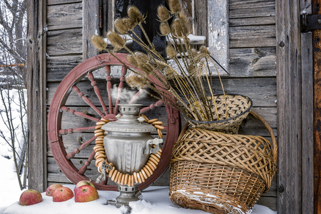 Rural still life. Hot samovar, steering-wheels, apples on the snow, spinning wheel, willow basket, straw pots with dry plants against the background of snow and an old wooden wall.