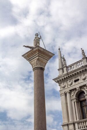 Italy, Venice. St. Marks Square. The capital of the column of Saint Theodore and part of the facade of the Cathedral of Saint Mark.