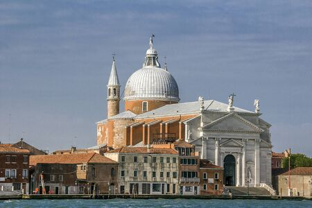 Italy, Venice. The Church Il Redentore is a church in Venice on the embankment of the island of Giudecca surrounded by residential and municipal buildings. May sunny day. Stock Photo
