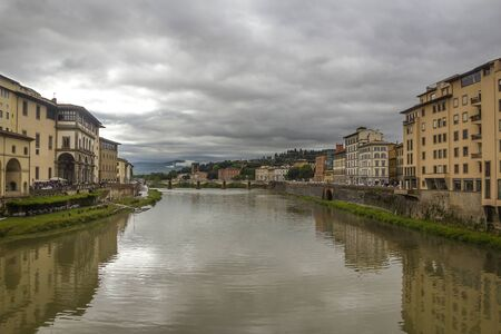 Italy, Florence, the capital of Tuscany. View from the Ponte Vecchio on the Arno River and the surrounding urban areas. Pre-storm May sky.