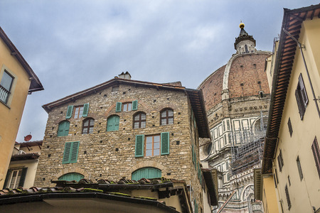Italy, Florence. Residential buildings on the background of the dome of the Cathedral of Santa Maria del Fiore, located in the heart of the city, on the Cathedral Square.