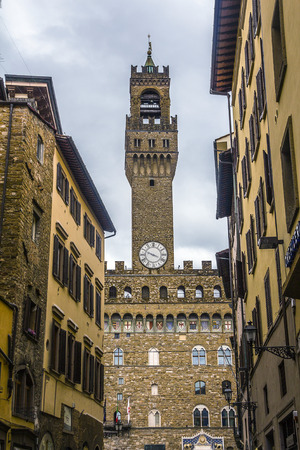 Italy, Florence. Palazzo Vecchio on Piazza Signoria. Clock tower on the background of pre-storm sky.