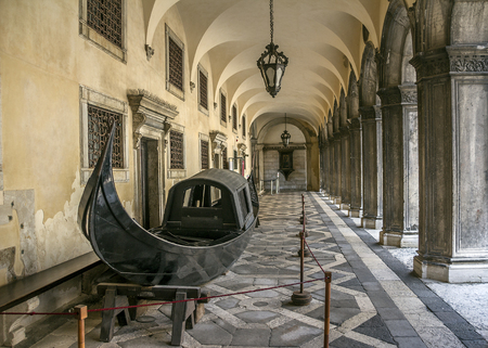 Italy, Venice. Courtyard of the Doges Palace with a colonnade and an ancient gondola. Editorial