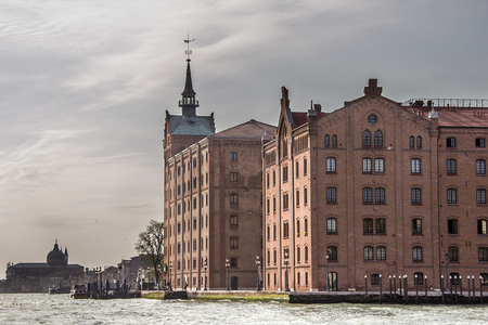 Italy, Venice. Former mill Stuсky on the island of Giudecca on the shore of the same channel. Cloudy May Day.