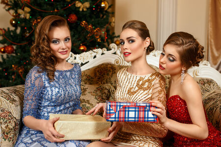 fashion women exchanging gifts in front of Christmas tree