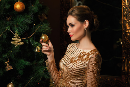 fashion woman hanged a  on the Christmas tree, stylized as gold