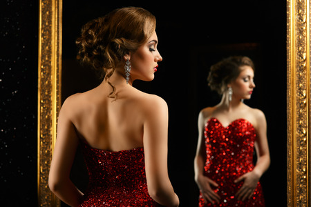 fashionable woman standing in front of gold mirror in red gown Stok Fotoğraf