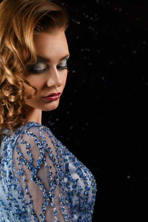 closeup fashionable woman in blue dress with rhinestones looking down photo