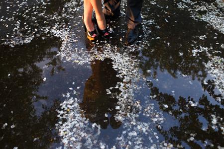 uomo sotto la pioggia: gambe di coppia in piedi vicino all'acqua con petali Archivio Fotografico
