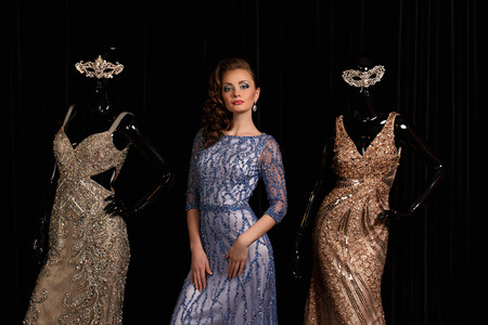 fashionable woman posing in blue dress with rhinestones and mannequins photo
