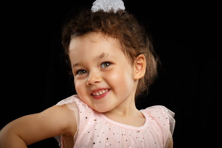 baby facial expressions: Close-up Portrait of 3 year old little girl with pink dress, shy on black background Stock Photo