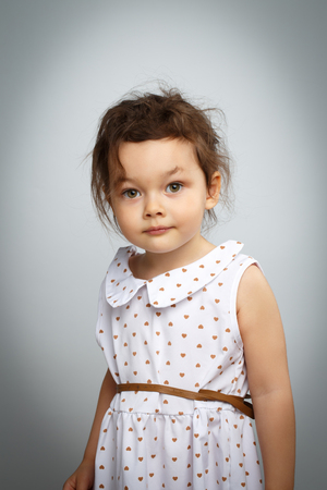 Portrait of 3 year old little girl with dress, surprised looks on bright white background Stock Photo