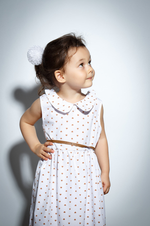 Portrait of 3 year old little girl with dress, looking up on bright white background Stock Photo