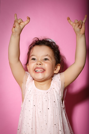 Portrait of 3 year old little girl with dress, showing horns on hands, dance screaming on rock concert on bright pink background Stock Photo