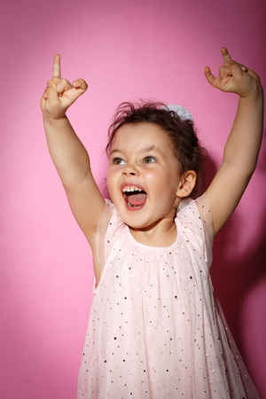 3 year old: Portrait of 3 year old little girl with dress, showing horns on hands, dance screaming on rock concert on bright pink background Stock Photo