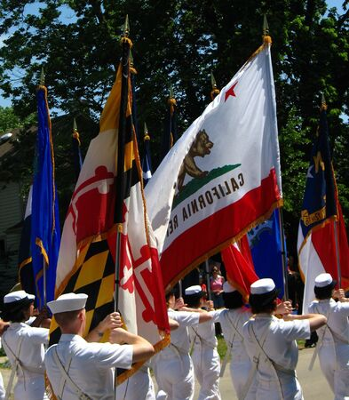 military personnel holding flags while marching in parade Stock Photo