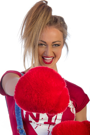 Extremely beautiful and sexy young adult caucasian woman playful with red ruf boxing gloves, isolated on white photo