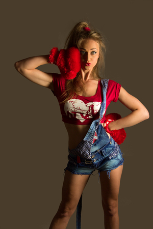 Extremely beautiful and sexy young adult caucasian woman playful with red ruf boxing gloves photo