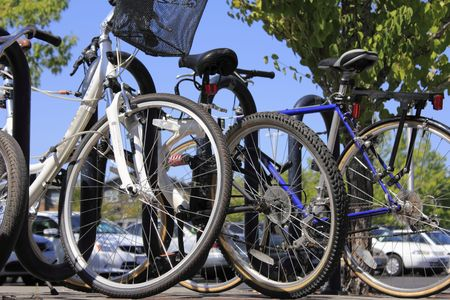 Close up view of bicycles locked to a bike rack and cars in a parking lot behind them. Stock Photo - 7584650