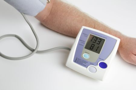 diabetic: Man measuring his own blood pressure Stock Photo