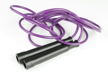 Black plastic handles with purple jump rope on a white background. Stock Photo