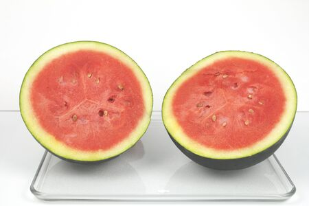 two and a half: A dark green organic watermelon cut in half. Stock Photo