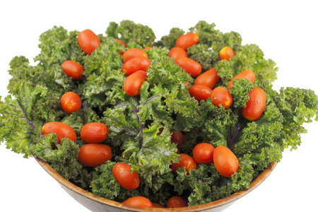 Small red cherry tomatoes on top of red kale in a wood bowl on white background. Stock Photo