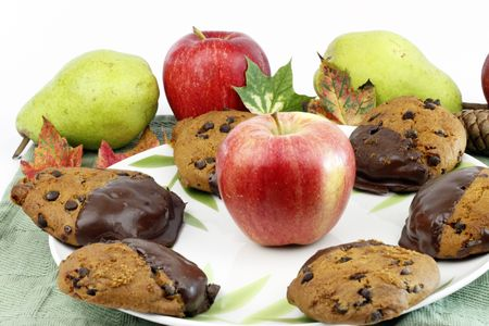 Fall treats dipped in chocolate surrounded by apples, pears, leaves, pine cone. photo