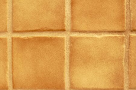 slightly: Slightly uneven hand-made ceramic surface decorations with warm tan grout in between.