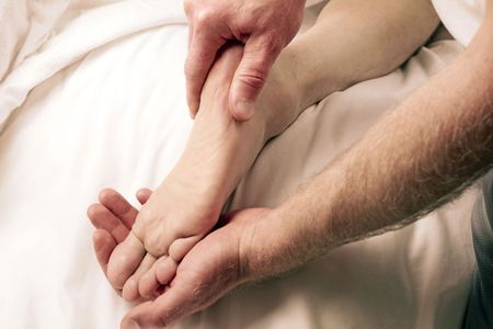 One mature guy receiving and one LMT giving foot massage therapy up close. Stock Photo