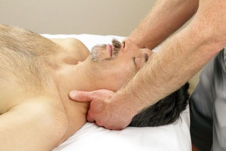 Male receiving massage therapy from hands of a man. photo