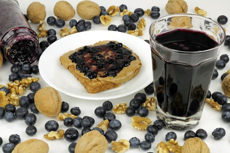 Blueberry preserves in jar on side and on almond butter on toast, blueberry juice, whole and shelled walnuts. Whole blueberries abstractly mixed with whole and shelled walnuts on reflective white surface.