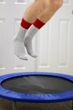 Male legs seen from knee down bouncing up in air above rebounder sport equipment.
