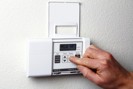 Fingers pushing control buttons on heating and cooling digital wall panel display.